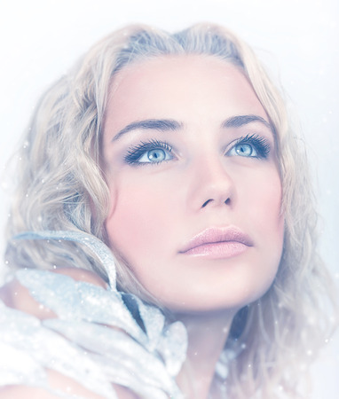 ice queen: Closeup portrait of gorgeous female with beautiful makeup holding decorative shiny leaves over snowy background, stylish look for Christmas