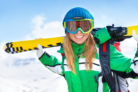 having fun in winter time: Portrait of cheerful smiling woman with ski equipment in snowy mountains, having fun outdoors in winter time, happy healthy lifestyle
