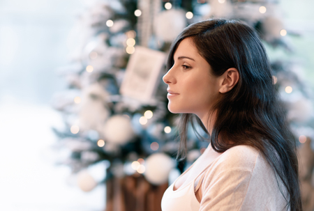 near side: Side view portrait of beautiful brunet girl near beautiful decorated Christmas tree, spending winter holidays at home