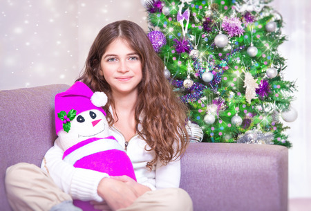 gift spending: Happy teen girl sitting near Christmas tree with snowman soft toy, enjoying gift, spending winter holidays at home Stock Photo