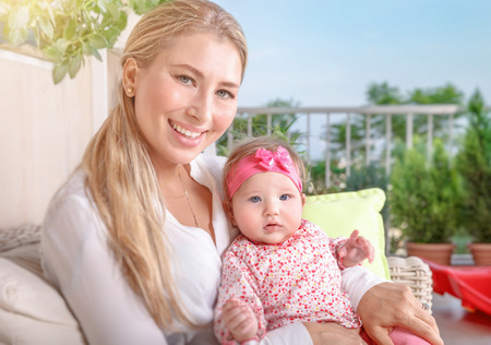domestic life: Cute mother with baby sitting on the balcony, young loving family with pleasure spending time outdoors, happy domestic life Stock Photo