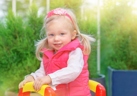 blond girl: Portrait of cute little blond girl having fun on playground in warm sunny day, adorable kid playing outdoors, happy carefree childhood