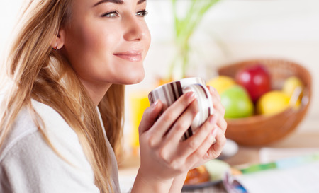woman bathrobe: Portrait of cute blond female having coffee in the kitchen, enjoying happy lazy morning, peace and relaxation at home Stock Photo