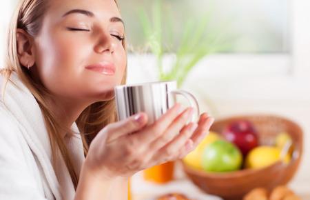 olfato: Retrato de mujer bonita con los ojos cerrados disfrutando de increíble aroma de café, desayunar sabrosa en casa, la vida doméstica feliz
