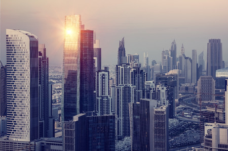 city panorama: Dubai downtown in the evening, luxury modern buildings in bright yellow sunset light, futuristic cityscape, expensive life in UAE Stock Photo