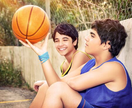two hands: Cute basketball players sitting and resting in timeout, two active teen boys enjoying outdoor games, happy youth lifestyle