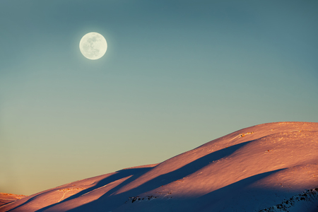 amazing stunning: Beautiful winter landscape, amazing view on the moon by day over mountains covered with snow, stunning wintertime nature
