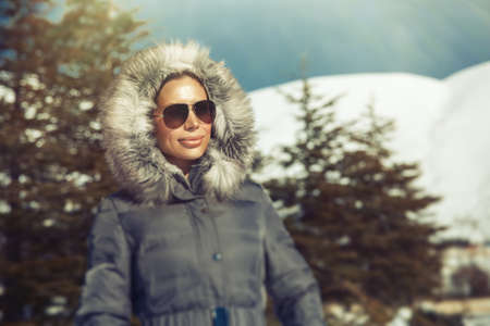 fur hood: Portrait of beautiful woman in the winter mountains, wearing warm coat with fur hood and stylish sunglasses