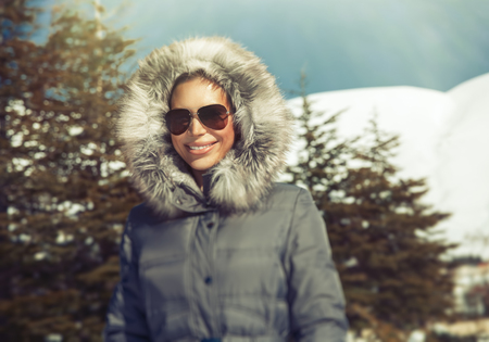 fur hood: Portrait of beautiful smiling woman in the snowy mountains, wearing warm coat with fur hood and stylish sunglasses, happy winter holidays Stock Photo