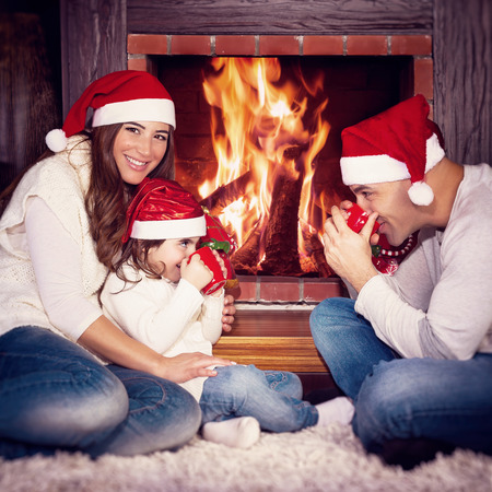 christmas spending: Lovely family sitting near fireplace and drinking tea, spending Christmas eve at home, happy winter holidays Stock Photo