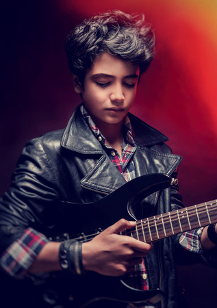 serious guy: Closeup portrait of serious teen guy playing on guitar in the studio over dark red background, interesting musical hobby