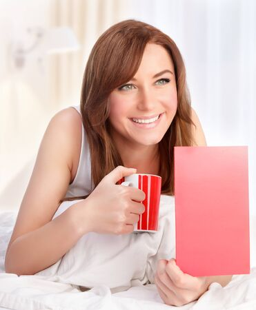 greeting card: Portrait of cute smiling female having coffee in the bed at home, with pleasure reading greeting card, happy Valentine day Stock Photo