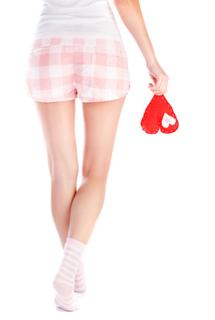 Back side of woman wearing pajamas holding red soft heart in hand, body part, isolated on white background, one-sided love concept