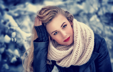 Closeup portrait of beautiful woman with red sexy lipstick posing in the winter park, gorgeous makeup, stylish look, wintertime fashion