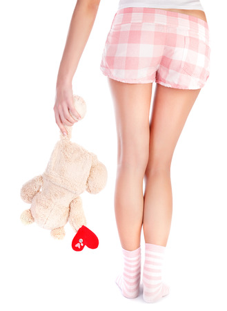soft toy: Back side of woman wearing pajamas holding soft toy of bear with red heart in hand, body part, isolated on white background, one-sided love concept