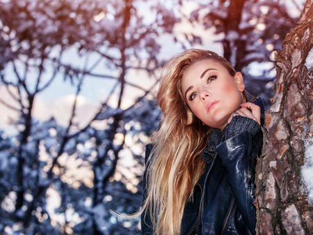 clothing model: Portrait of beautiful blond woman standing near tree in the winter park, fashionable clothing, gorgeous model posing outdoors