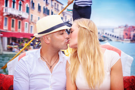 relationship love: Portrait of happy loving couple in romantic honeymoon, kissing on a gondola, vacation in Italy, enjoying holidays in Europe