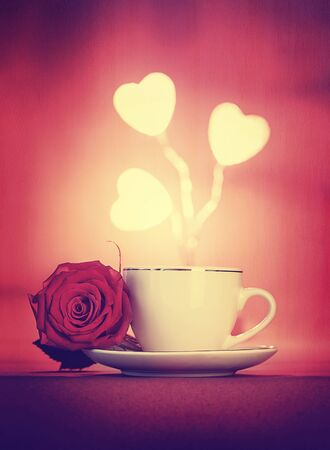 valentine day cup of coffee: Beautiful romantic still life, morning coffee decorated with fresh rose flower and glowing hearts over red background, vintage style greeting card for Valentine day