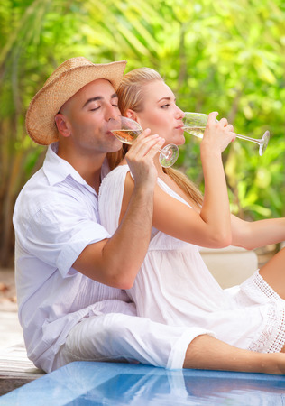 tropical drink: Two people in love sitting near swimming pool on the beach resort and drinking champagne, romantic honeymoon vacation Stock Photo