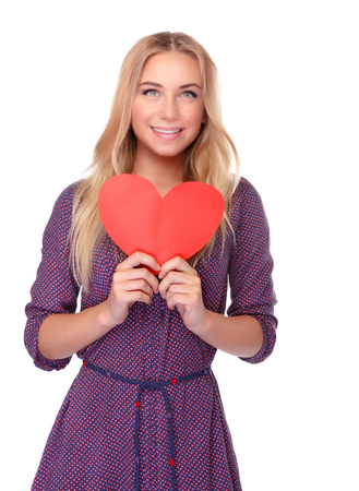 feel affection: Cute girl with red paper heart in hands isolated on white background, symbol of health and love, celebrating Valentine day Stock Photo