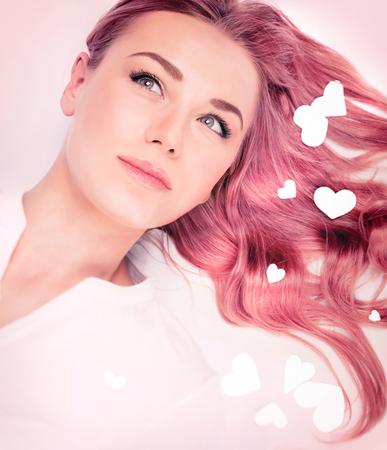 Portret kobiety mody, pomysł włosy na Walentynki, elegancki różowy pastelowy kolor włosów, modne fryzury faliste długie, piękne modelu z romantycznym wyglądzie