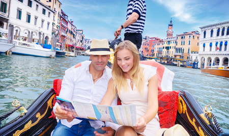 Loving couple traveling to Venice, searching on the map place with famous sightseeing, riding on a gondola on the Grand Canal, vacation in Italy, enjoying holidays in Europe