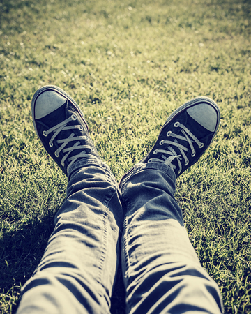 people relaxing: Closeup photo of lazy teen guy lying down on green grass an wearing stylish trendy gumshoes, body part, relaxing outdoors, sportive shoes, fashion for hipster