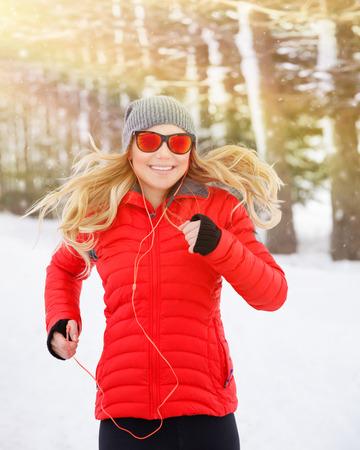 escucha activa: Retrato de la hermosa corredor feliz al aire libre, hembra rubia linda que se ejecuta en el parque de invierno y escuchar m�sica en los auriculares, estilo de vida activo y saludable