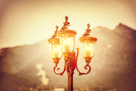 europe vintage: Beautiful vintage street lamp glowing in the evening over high mountains background, amazing antique architecture detail, Seefeld, Austria, Europe