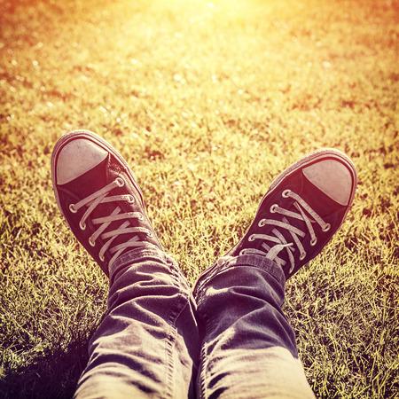 perezoso: Foto de cerca de chico adolescente perezoso tumbado en la hierba verde y el uso de sabuesos de moda con estilo en la luz brillante del sol amarilla, parte del cuerpo, relajarse al aire libre, la moda de última moda Foto de archivo