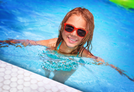 cute baby girls: Portrait of cute happy little girl having fun in swimming pool, adorable baby spending summer vacation on the beach resort