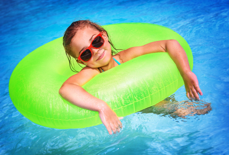 rubber ring: Portrait of cute happy little girl having fun in swimming pool, floating in blue refreshing water with big green rubber ring, active summer vacation on the beach