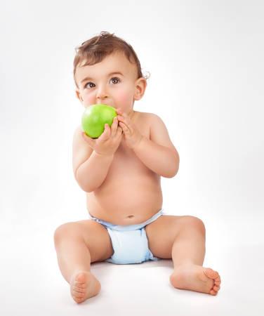 manzana verde: Pequeño bebé lindo que se sienta en el estudio sobre fondo blanco y comer manzana verde fresca, feliz infancia saludable