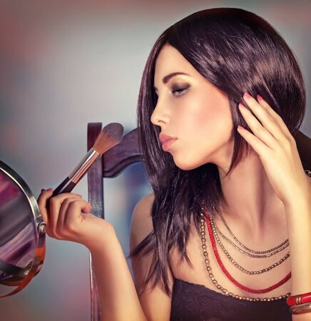 attractive gorgeous: Fashion woman portrait, attractive girl looking in the mirror and doing stylish makeup, preparation to party, gorgeous fashionable look Stock Photo