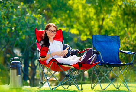 celling: Pretty woman spending time outdoors, sitting in armchair with phone in hands, enjoying vacation in the camping, relaxation in countryside