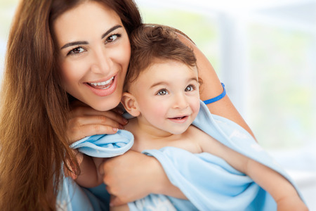 madre e figlio: Ritratto del primo piano di bella madre allegra azienda in mani piccolo figlio dopo il bagno avvolto in un asciugamano, igiene del bambino, felice stile di vita sano