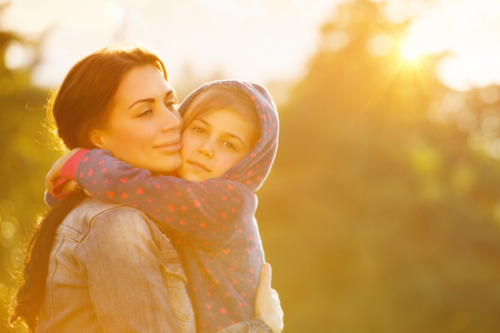 Portrait of beautiful mother with love hugging her precious daughter in bright yellow sunlight in the park, happy family life 스톡 콘텐츠