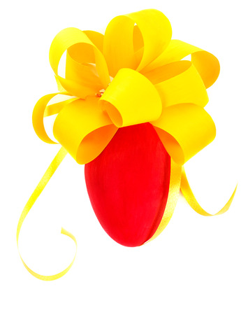 holiday tradition: Closeup photo of beautiful red drawing egg with festive yellow bow isolated on white background, tradition symbol of Easter holiday