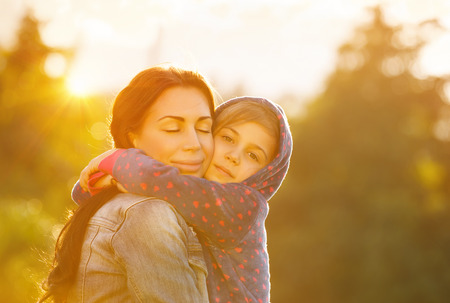 Familia feliz junto, joven madre hermosa cerrar los ojos en el placer que abraza a su pequeña hija linda, brillante día soleado, la maternidad feliz
