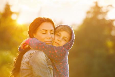 personas abrazadas: Familia feliz junto, joven madre hermosa cerrar los ojos en el placer que abraza a su pequeña hija linda, brillante día soleado, la maternidad feliz Foto de archivo