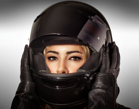 Closeup portrait of beautiful biker woman over gray background, sexy female with glamorous makeup wearing stylish black protective sportive helmet and leather gloves photo