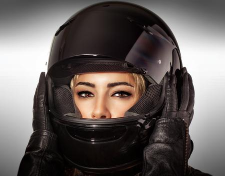 casco moto: Retrato de mujer hermosa motorista sobre fondo gris, femenino atractivo con maquillaje de glamour con estilo deportivo casco de protección y guantes de cuero negro Foto de archivo