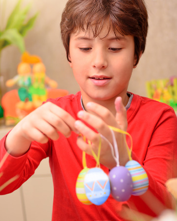 anticipate: Portrait of cute boy play with beautiful colorful decorated eggs at home, with pleasure anticipate happy Easter holiday