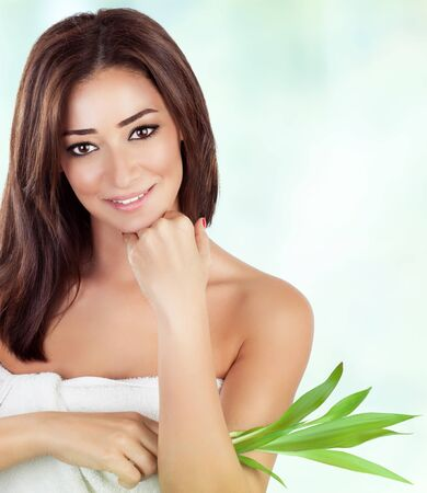 Portrait of gentle female holding fresh green leaves over blur and white background, with pleasure spending day in luxury spa salon photo