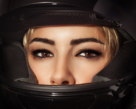Closeup portrait of beautiful biker woman, sexy female with glamorous makeup wearing stylish black protective sportive helmet