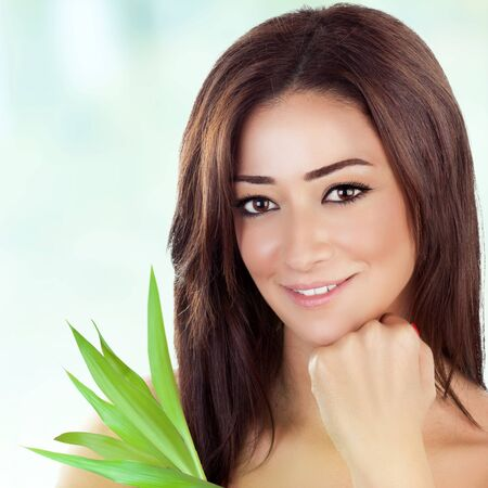 Closeup portrait of beautiful brunette woman with fresh green leaves over blue blur background, healthy lifestyle, enjoying day spa photo