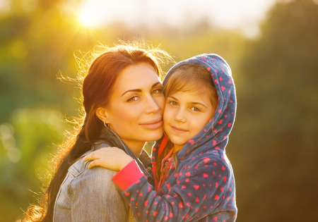 Portrait of beautiful young mother with her cute little daughter outdoors in bright sun light, spending time together in the park, happy loving family