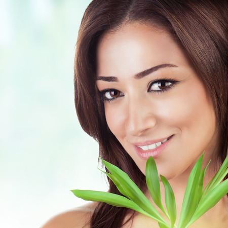 Closeup portrait of beautiful brunet woman with fresh green leaves over blue blur background, healthy lifestyle, enjoying day spa photo