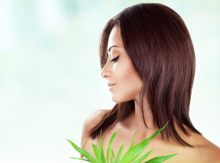 Side view of gentle female with closed eyes posing over blur and white background, holding fresh green leaves, spending day in luxury spa salon photo