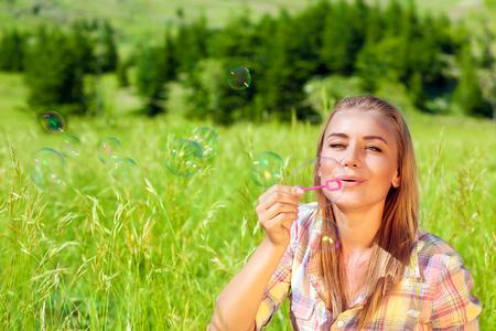jabon: Retrato de mujer que se divierten al aire libre, sentado en campo de hierba verde fresca y con gusto soplando pompas de jabón feliz, disfrutando de la vida linda
